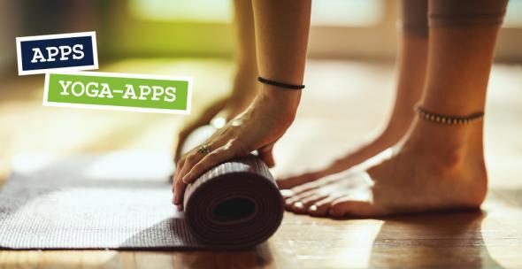 Eine Frau rollt eine Yoga-Matte aus.