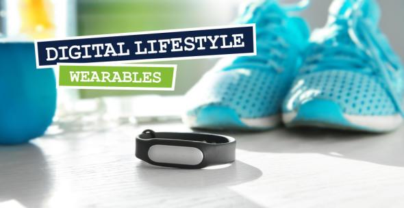 Blaue Turnschuhe und ein Fitnesstracker-Armband als Wearbale