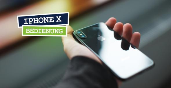 Ein iPhone X wird in der Hand gehalten mit dem Display nach unten und dem Logo nach oben.