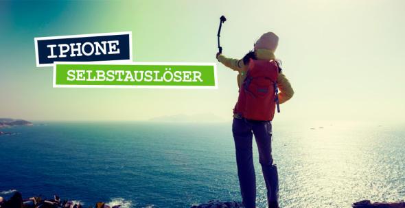 Junge Frau die an der Küste steht und einen Selfiestick in der Hand hält.