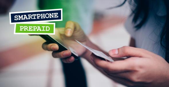 Eine Person mit einem Smartphone und einer Prepaid-Karte in der Hand.