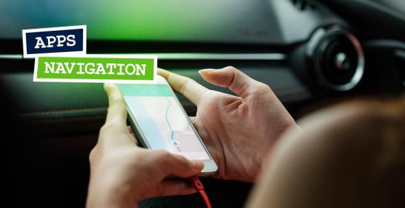 Smartphone in der Hand einer Person im Inneren eines Wagens.