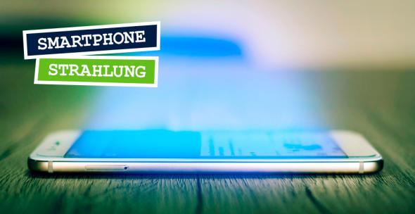 """Ein auf Holzuntergrund liegendes Smartphone, das Licht abstrahlt - Symbolbidl für """"Handystrahlung""""."""