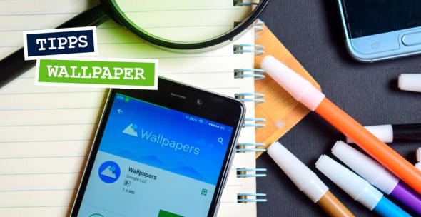 Ein Handy, auf dem eine Wallpaper-App geöffnet ist, liegt auf einem Block neben Stiften.