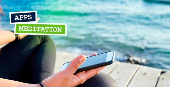 Mensch im Meditationssitz mit Smartphone in der Hand.