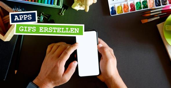 Hände halten ein Smartphone über einen Schreibtisch, der mit Farben, Stiften und Pinseln bedeckt ist.