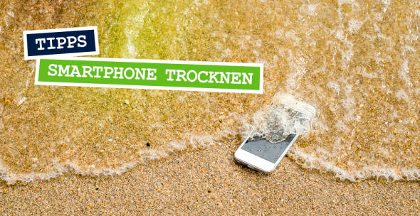 Ein Handy, das am Strand von Wasser umspült ist.