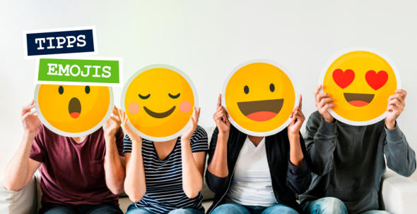 Vier Menschen, die sich vier verschiedene Emojis aus Papier vor Ihre Gesichter halten.