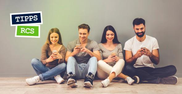 Zwei Männer und Frauen sitzen auf dem Boden mit ihren Smartphones.