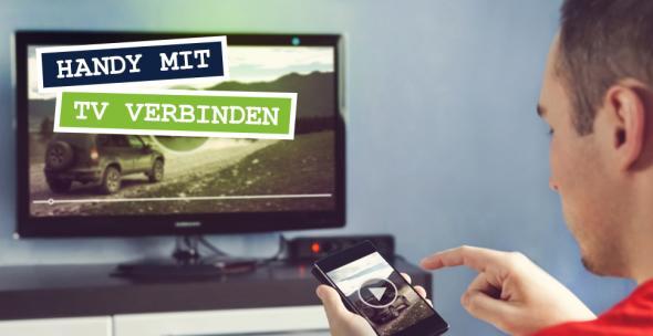 Ein Mann verbindet das Smartphone mit dem Fernseher.