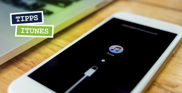 Auf einem iPhone-Display wird angezeigt, dass das iPhone mit iTunes verbunden ist.