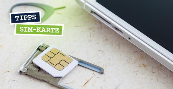 Eine SIM-Karte neben einem Smartphone.