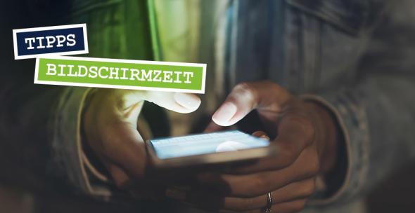 Eine Frau hält im Dunkeln ein Smartphone in der Hand.